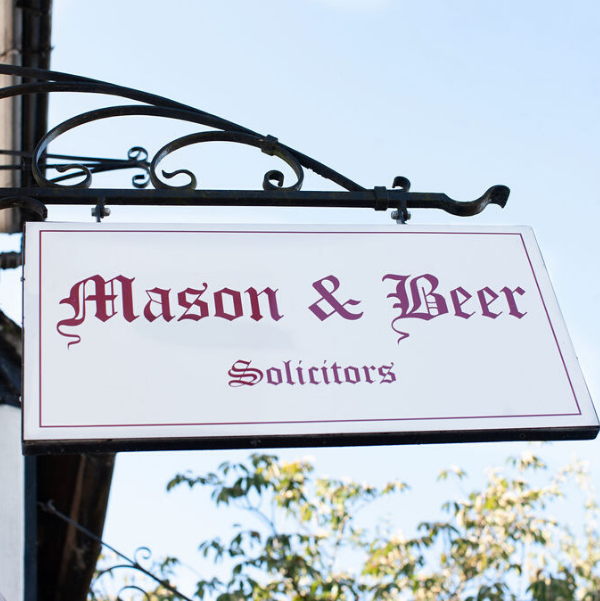 White sign on black iron hanging bracket with Mason & Beer Solicitors written in red.