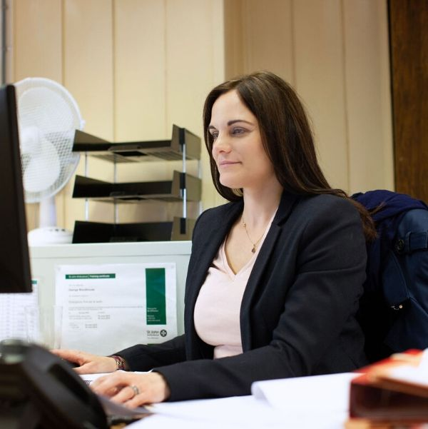 Solicitor Laura Harwood sitting at her desk and using a computer