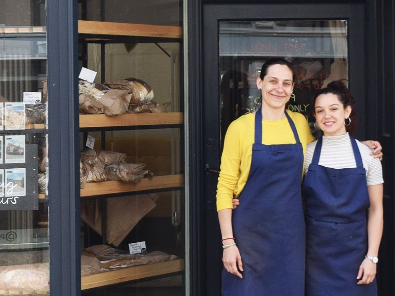 Two female business owners standing on front of a bakery door