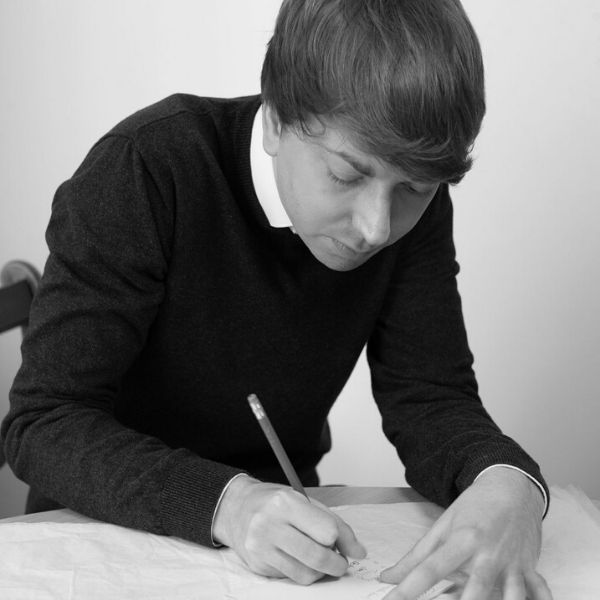 Black and white picture of Solicitor George Woodhouse leaning over a document with a pencil in hand