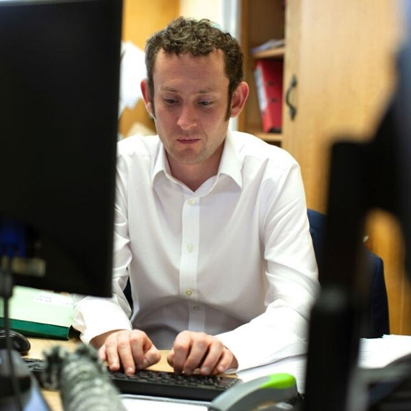 CILEX Associate James Pitcairn typing on computer sitting at his desk
